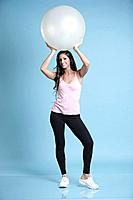 Young woman holding exercise ball over head