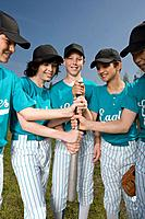 Little league players holding baseball bat