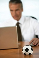 Senior businessman using a laptop, small soccer in foreground