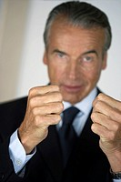 Senior businessman pressing thumbs