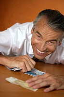 Laughing businessman bending of banknotes