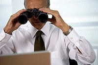 Senior businessman looking through a field glass to a laptop