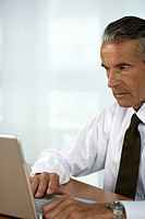 Concentrated senior businessman using a laptop