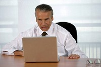 Nervous senior businessman using a laptop