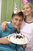 Mature man with a birthday cake in his hand next to his blond daughter, both wearing cornets, close_up