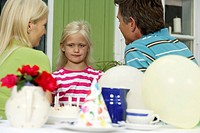 Blond girl between her parents looking discontented, selective focus