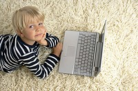 Boy 4_5 Years lying on floor with a laptop, looking at camera