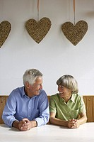 Senior adult couple sitting under a decoration of cork hearts while smiling at one another