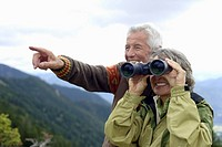 Senior adult couple with binoculars in the mountains, close_up, selective focus