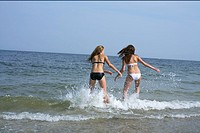 Two young women in bikini running into the sea, blurred motion