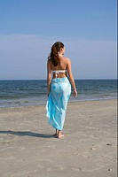 Young brunette woman promenading at the beach