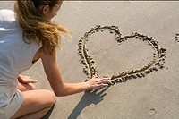 Blond woman painting a heart into the sand with her finger, high angle view (thumbnail)