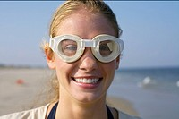 Young woman with diving goggles at the beach, selective focus