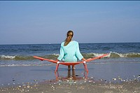 Woman sitting on a beach chair while looking at the sea