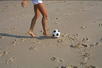 Young woman playing football at the beach part of, high angle view