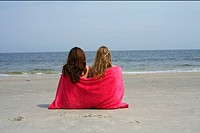Two young women sitting next to each other at the beach with a towel over their back