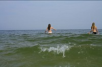 Two young women in bikini walking into the sea, blurred motion