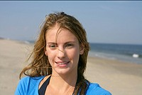 Young blond woman with wet hair at the beach, close_up, selective focus