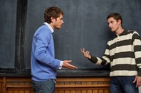 Two young men debating in front of a blackboard, low angle view