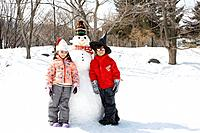 Children standing by a snowman