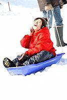 A boy using mobile phone on the sled