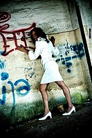 young dark_haired woman posing at wall with graffiti