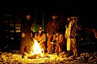 Wranglers gathered by the evening fire in the snow, Shell, Wyoming. Usa