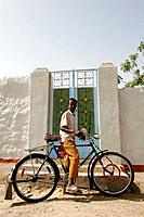 In Kerma a young boy on a very colored bicycle in front of a nubian house