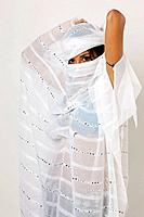 Young Latin model in her 20s dressed as an arab dancer hiding her face with a veil