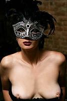 Young nude woman wearing costume mask