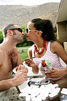 Young couple kissing at pool party.