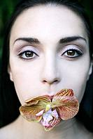 Young woman with orchid in mouth