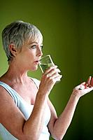 Mature woman drinking glass of water with pills.