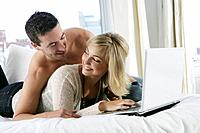Young happy couple using laptop in bed