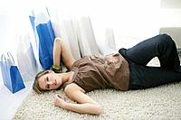 Young woman relaxing on floor with shopping bags