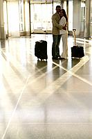 Young couple standing in airport with luggage