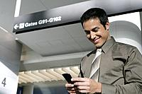 Young businessman text messaging in airport