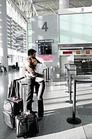 Young couple hugging in airport (thumbnail)