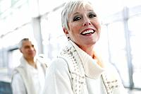 Happy mature woman at airport with man behind.