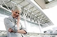 Happy mature woman on the phone in front of airport