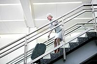 Mature woman pulling luggage upstairs in airport (thumbnail)