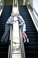 Mature couple kissing on escalators (thumbnail)