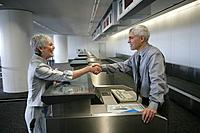 Check in attendant and passenger shaking hands at airport check in counter