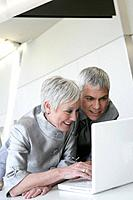 Happy mature couple looking at laptop in airport