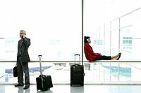 Businessman and African_American woman waiting at airport.