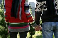 Rear view of couple holding hands outdoors