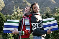Young couple holding Christmas boxes