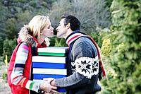 Couple with Christmas boxes about to kiss