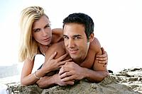 Young nude couple relaxing on beach