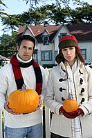 Young couple holding pumpkins outdoors.